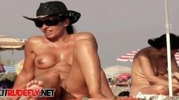 Una nudista filmada por un voyeur se hace un bronceado desnuda en la playa