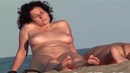 Una simpática milf nudista espiada por un fisgón en la playa