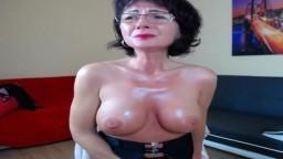 Una mujer madura con grandes pechos de silicona masturbándose en la web